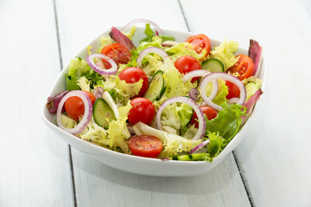 Dish of fresh salad with courgettes, onion, lettuce and cherry tomatoes