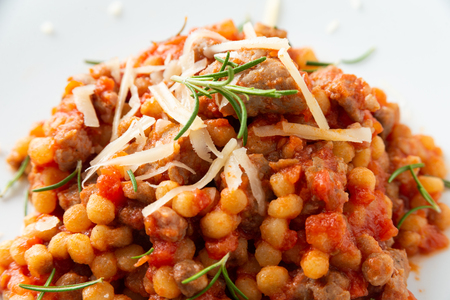 Dish of fregola pasta with sausage and tomato sauce