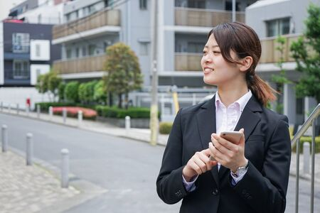 Young businesswoman searching for a destination with her smartphone