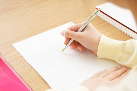 Young woman write something on white paper