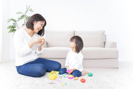 Child playing with toy with mother Standard-Bild