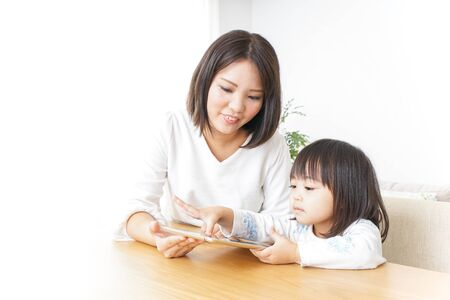 Child using smartphone with mother