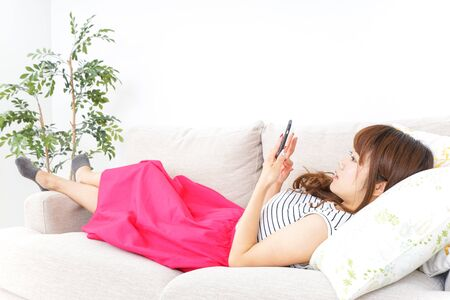Young woman using smart phone at home