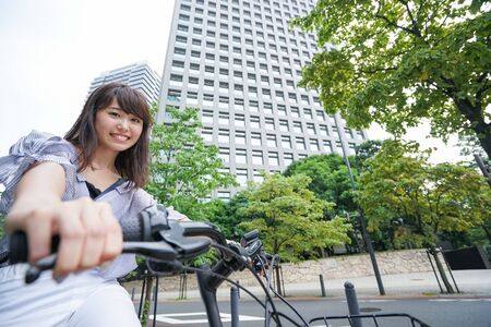 Woman ridin electric cycle with child Imagens
