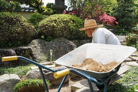 Elderly man planting a garden 写真素材 - 128876673