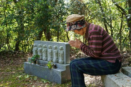 Elderly woman visiting the family grave