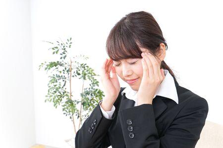 mujer de negocios que sufre de dolor de cabeza