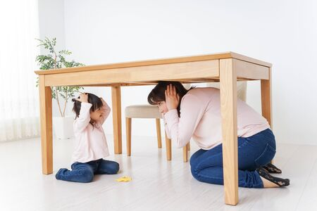 A parent and child huddling under a table Imagens