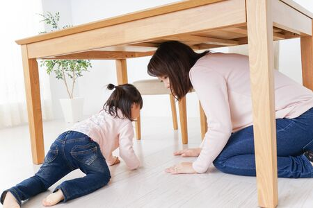 A parent and child huddling under a table Stock Photo