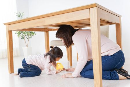 A parent and child huddling under a table Stock fotó