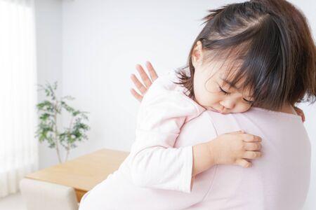 Bambino addormentato portato dalla madre