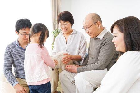 Three-generation family taking care of dog 写真素材