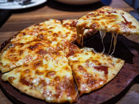 Pizza garnished with cheese on a wooden board.