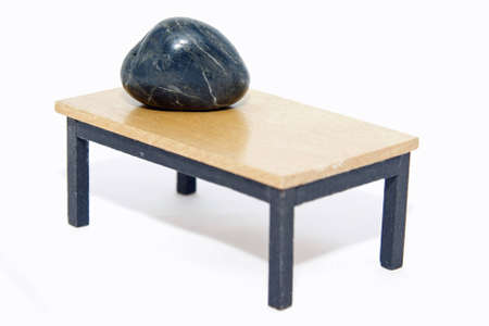Stone is on the edge of the table Stock Photo