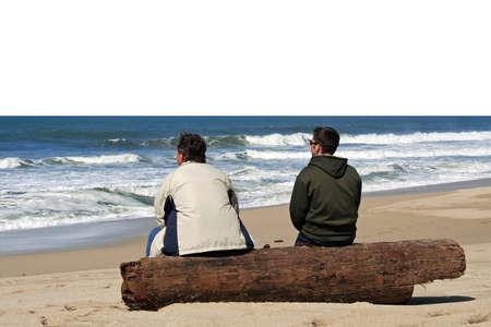 Due uomini seduti in spiaggia e parlando