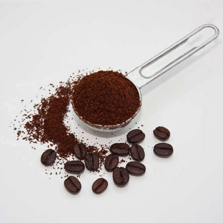 Coffeebeans and grounded coffee with a measure spoon