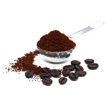 polvos: Coffeebeans y caf� tierra con una cuchara de medida Foto de archivo