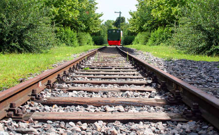 Railroad tracks with a steam locomotive at the end Stock Photo