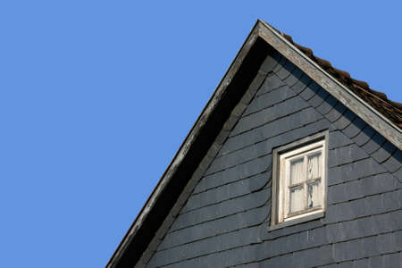 Part of a roof with a wooden window with blue background