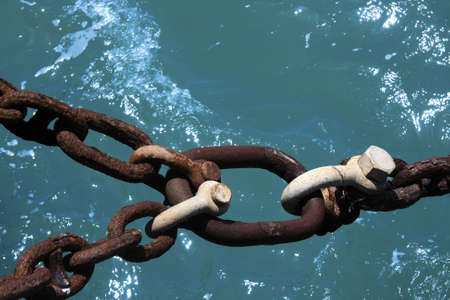 Rusty iron-chain with three shackles over water Stock Photo