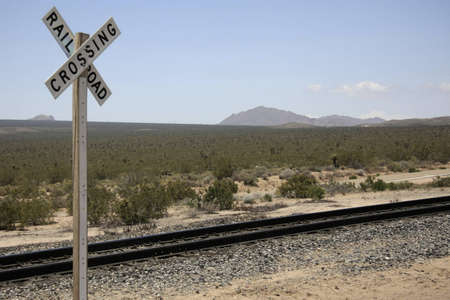 Railroad track in the desert with sign railroad crossing