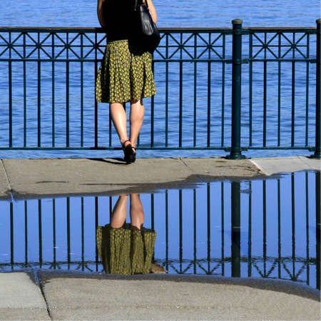 Woman is standing close the ocean, legs are reflecting in a puddle photo