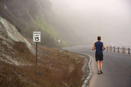 Man is running on a street into the fog