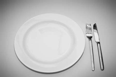 Piatto bianco con forchetta e coltello su sfondo bianco sfumato