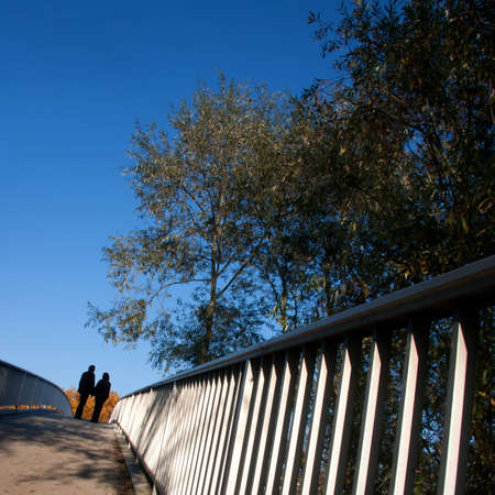Silhouette of a couple standing on a bridge from lower angle photo