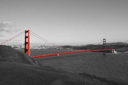 Red Golden Gate Bridge with San Francisco in background in black and white photo