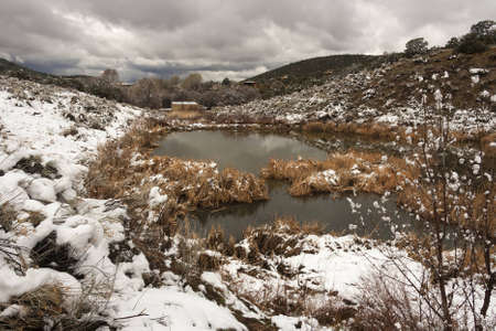 Landscape picture of a reservoir in the desert with snow and clouds photo