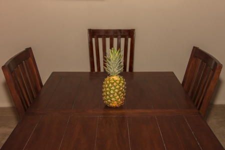 A pineapple on a rustic dinner table