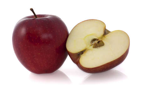 A whole red apple and a half of an apple at the right Stock Photo