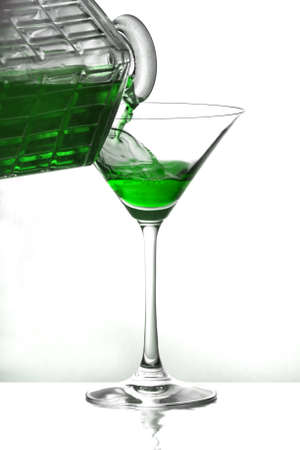 Pouring a green liquid into a cocktail glass over white photo