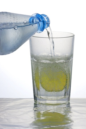 Pouring sparkling water into a caipirinha glass with a lemon slice photo