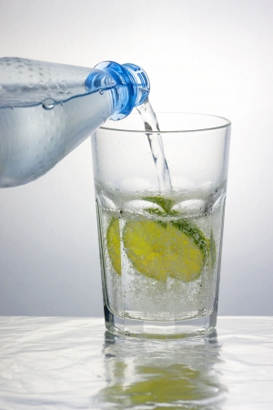 Pouring sparkling water into a caipirinha glass with a lemon slice