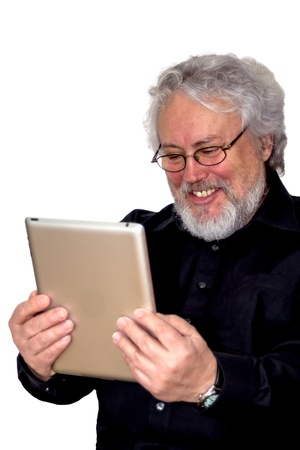 A senior with grey hair is holding a tablet and looking at it laughing photo