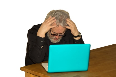 A senior is sitting in front of a laptop computer desperate Stock Photo - 18468288