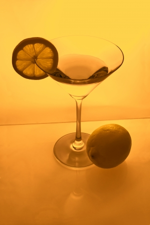 Martini glass with lemon slice and lemon from above in amber light photo