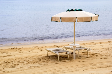 Two chairs and an opened umbrella at the sandy beach photo