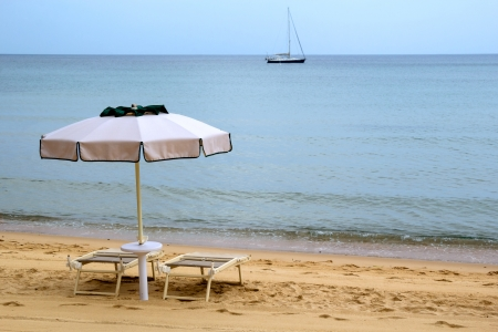 Two chairs and an opened umbrella at the sandy beach and sailboat in blurred background photo