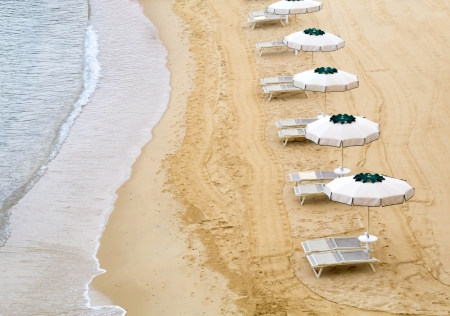 Deserted beach with open umbrellas at the ocean from above photo