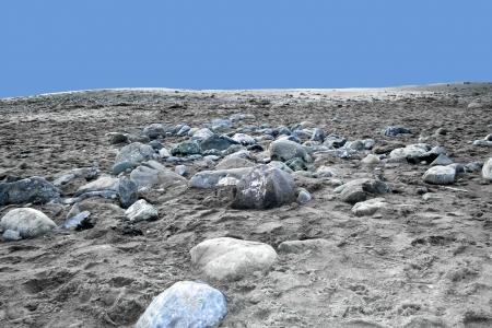 Ciottoli su una spiaggia di sabbia dall'angolo basso
