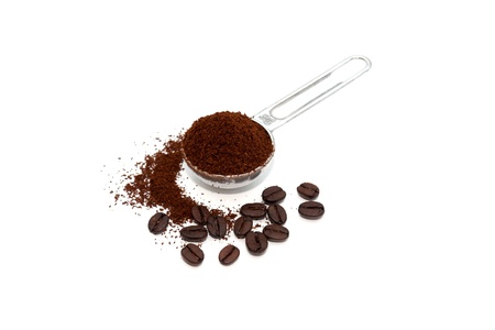 Grounded coffee in a spoon surrounded with beans isolated