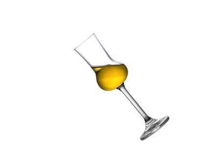 A tilted half full grappa glass isolated on white