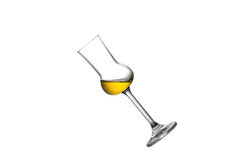 grappa: A tilted slightly filled grappa glass isolated on white