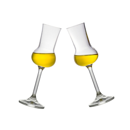 Two toasting filled Grappa glasses isolated on white
