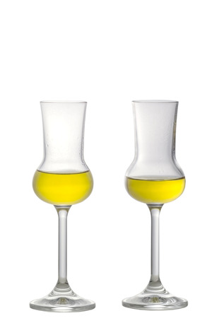 Two filled Grappa Glasses standing upright isolated on white