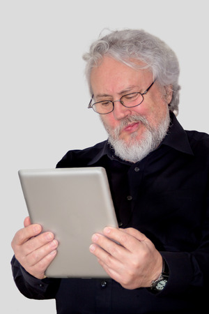 A senior with grey hair is holding a tablet and making a face at it