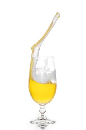 Splashing beer in a glass with little foam photo